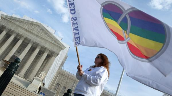 Same-sex marriage proponent Kat McGuckin of Oaklyn, N.J., holds a gay marriage pride flag in front of the Supreme Court Nov. 30, 2012. The court says it will review two cases related to same-sex marriage in 2013.