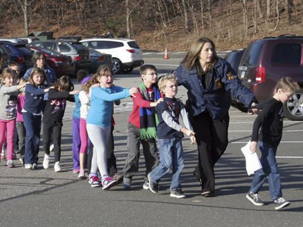 In this photo provided by the <em>Newtown Bee</em>, Connecticut State Police lead children from the Sandy Hook Elementary School in Newtown, Conn., following a shooting there Friday.