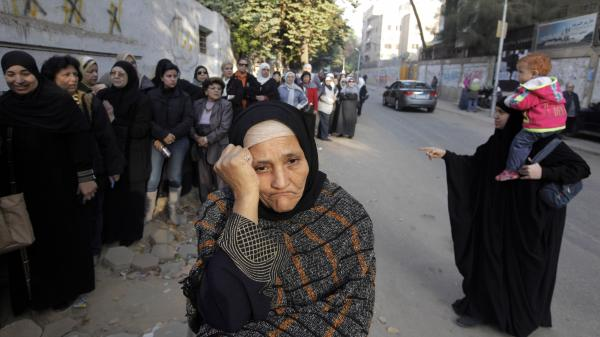 Women wait in line outside a polling station to vote on a disputed constitution drafted by Islamist supporters of President Mohammed Morsi in Cairo on Saturday.