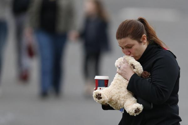 A woman kisses a stuffed animal before placing it on the memorial.