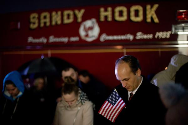 Mourners outside Newtown High School listen to a memorial service over a loudspeaker, on Sunday evening.