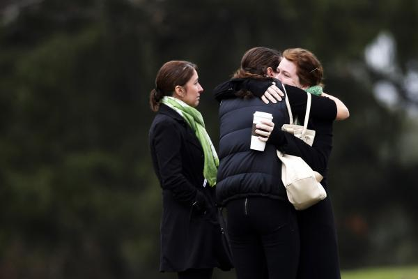 Mourners embrace as they leave the Honan Funeral Home, where the family of Jack Pinto was holding his funeral service on Monday.