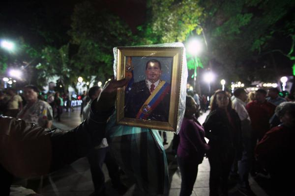 A man holds up an image of Chavez as people gather to pray for him at Simon Bolivar Square in Caracas on Dec. 11, 2012. Chavez was in Cuba at the time for cancer treatment.
