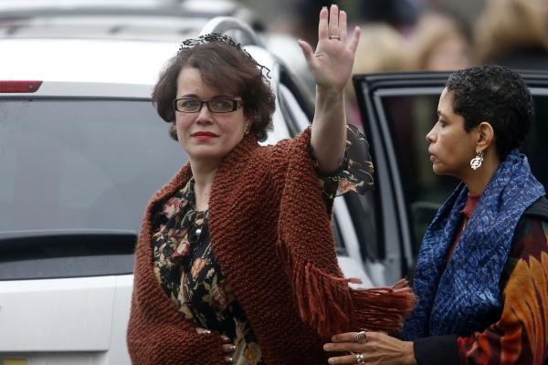 Veronique Pozner waves to the members of the press as she leaves after a funeral service for her son, 6-year-old Noah Pozner in Fairfield, Conn. Noah was one of 20 students killed in the shootings on Friday.