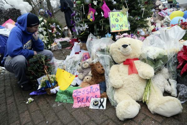 A mourner pays his respects at one of the makeshift memorials for the Sandy Hook elementary shooting on Monday in Newtown, Conn.