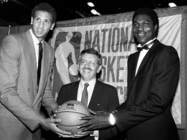NBA commissioner David Stern is flanked by Akeem Olajuwon (right), the No. 1 pick overall by the Houston Rockets, and Sam Bowie, the No. 2 pick overall by the Portland Trail Blazers, at the NBA Draft in New York on June 19, 1984.