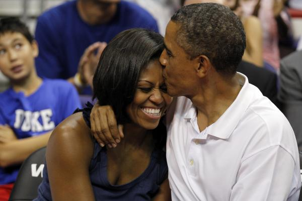 "<strong>Aww:</strong> Obama sneaks an extra smooch after kissing Michelle for the ""Kiss Cam"" at the basketball game between U.S. and Brazil, on July 16, 2012, in Washington, D.C."