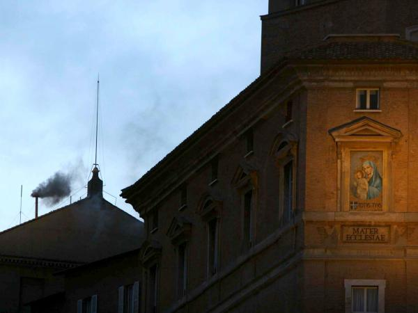Black smoke rises from the chimney of the Sistine Chapel on April 18, 2005. Black smoke signaled that the cardinals sequestered inside had failed to elect a new pope, after the death of Pope John Paul II.