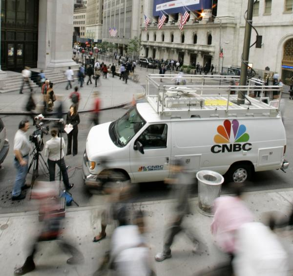 Morning rush hour commuters pass by a CNBC crew in front of the New York Stock Exchange in September 2006. The channel has adopted a policy that prohibits guests from appearing on rival channels amid breaking news.