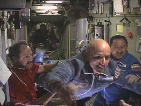 Dennis Tito (center) flies into the International Space Station as Russian Talgat Musabayev (right) looks on and the station's Russian commander, Yuri Usache, welcomes them, on April 30, 2001.