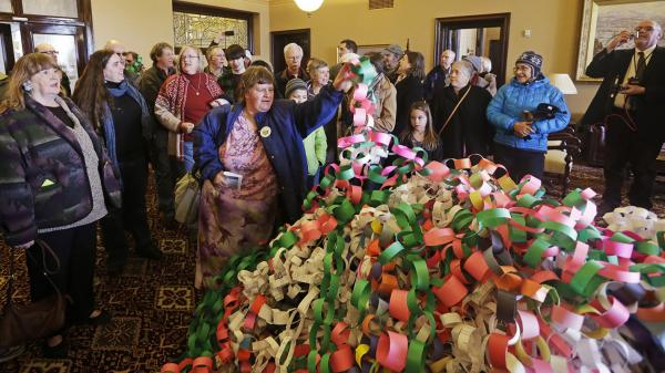 Outside the office of Utah Gov. Herbert Friday, Betsy Ogden lays paper chains on a pile symbolizing uninsured state residents who would be covered by a Medicaid expansion.