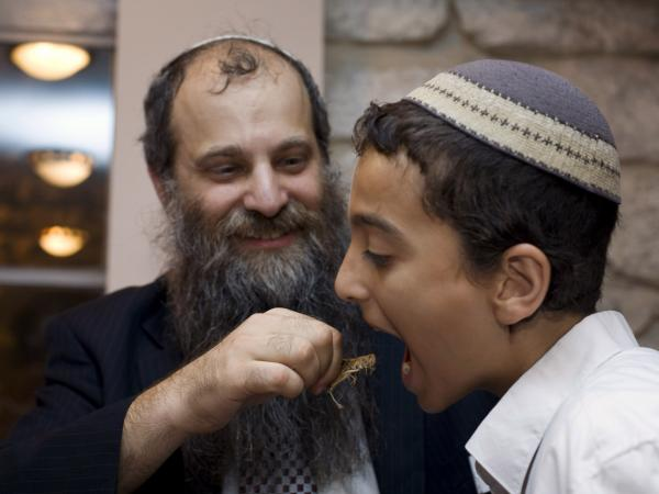 An Israeli Orthodox Jewish man mimics putting a locust into a boy's mouth, during an event meant to highlight locusts as a kosher treat, at a restaurant in Jerusalem in 2010.