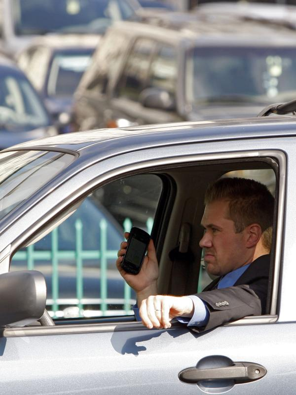 A driver uses a cellphone while driving Wednesday, Dec. 14, 2011, downtown Los Angeles.