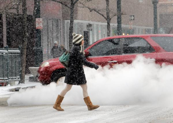 A woman crosses the street as steam rises from a manhole cover in Denver's financial district on Tuesday.