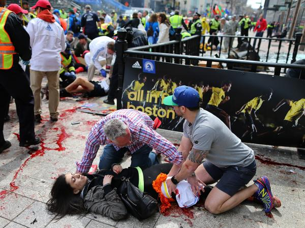 Bystanders help Sydney Corcoran at the scene of the first explosion near the finish line of the 117th Boston Marathon.