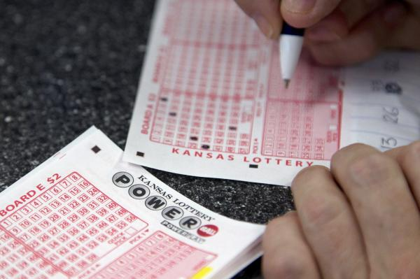 A customer fills out a Powerball form at the Jayhawk Food Mart in Lawrence, Kan., last Nov. 23, 2012.