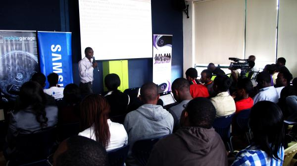 "Kenyans watch a presentation at the ""mobile apps garage showcase"" this in Nairobi."