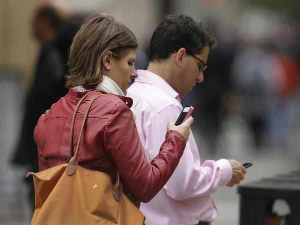 People use cellphones in downtown San Francisco. The city's district attorney and New York's attorney general plan to meet with major cellphone manufacturers, as they push the industry to do more to protect consumers from violent street crimes connected to cellphone thefts.