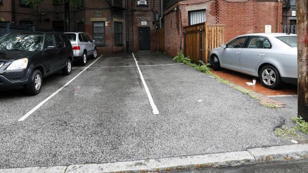 Parking spaces behind 298 Commonwealth Avenue in Boston are seen Friday. The two open spaces at right, front and back, were sold at auction for $560,000.