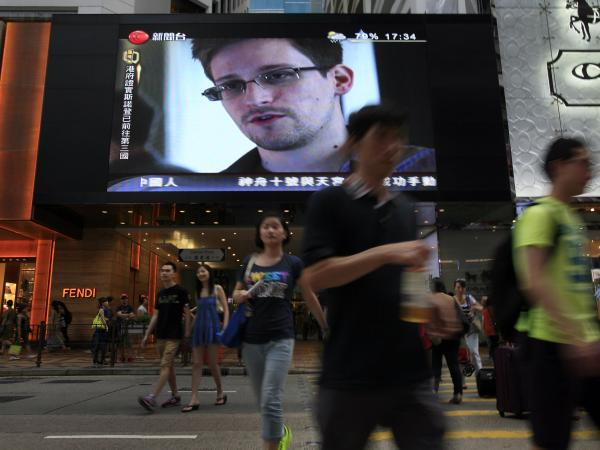 A TV screen shows a news report of Edward Snowden at a shopping mall in Hong Kong on Sunday.