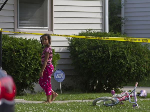 A young neighbor watches as police respond to a double homicide in Flint, Mich., on June 30. Organizations including the Michigan Youth Violence Prevention Center are working to help young people choose non-violent solutions to conflict.