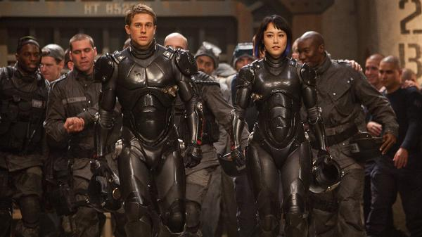 Charlie Hunnam and Rinko Kikuchi are the human co-pilots who mind-meld to control the giant Jaegers — massive robots engineered to fight rampaging sea monsters — in <em>Pacific Rim</em>, a <em>kaiju</em>-film homage from director Guillermo del Toro.