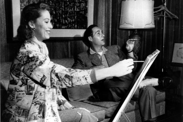 Caesar relaxes while his wife, Florence, paints a portrait of him in their Kings Point, N.Y., home in 1958. Sid's new weekly program, <em>Sid Caesar Invites You,</em> premiered that year.