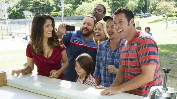 Improbably or not, Salma Hayek (left) and Adam Sandler (far right) are a couple again in <em>Grown Ups 2.</em> Billed as a comedy, the film also features Kevin James, Alexys Nicole Sanchez, Chris Rock, Maria Bello and David Spade, who in this scene are all pretending to laugh at something that in all likelihood involves poo.