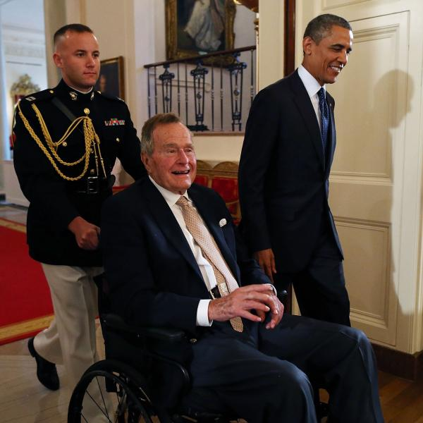 Former President George H. W. Bush, in a wheelchair, as he was escorted into the East Room of the White House on Monday by President Obama.