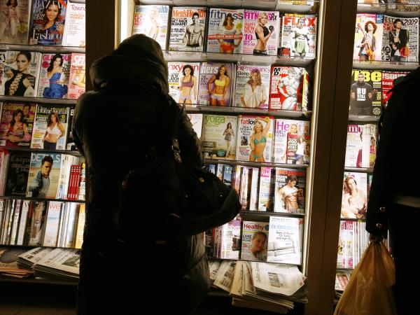 Customers browse for English-language magazines and newspapers at a New York newsstand.
