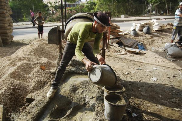 A construction worker mixes concrete by hand at a building site in the Gaza Strip.