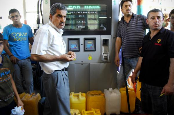 Gazans wait for a turn at the gas nozzle. Fuel is critical to run generators that families, shops and hospitals use for the extensive periods when electricity is unavailable.