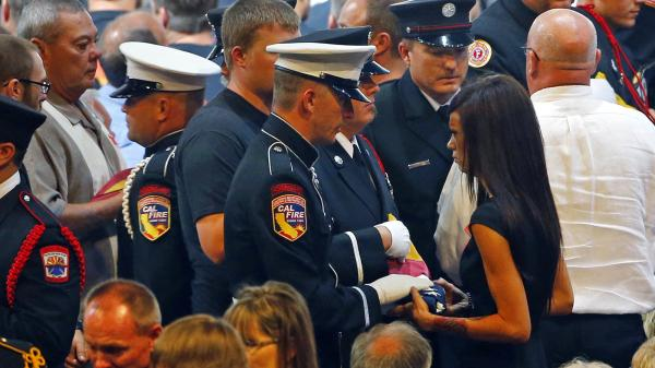 Juliann Ashcraft, wife of late firefighter Andrew Ashcraft, receives a U.S. flag during a memorial service in July. Ashcraft says the city has refused to pay full benefits for her husband's death, calling him a seasonal employee.