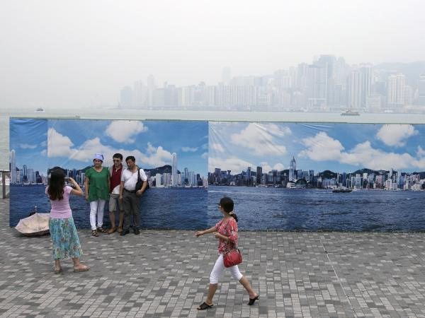 Tourists from mainland China take photos in front of a large outdoor banner showing what Hong Kong looks like on a clean air day, in Hong Kong on Aug. 21.