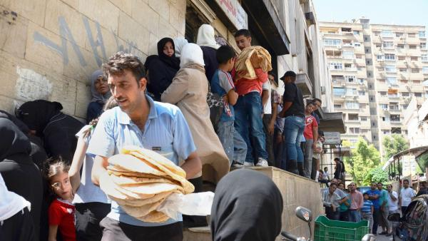 Shoppers form a line at a bakery in Damascus, Syria, on Friday. Ahead of President Obama's speech Saturday, the price for a bag of pita bread shot up amid speculation of a U.S. military strike.