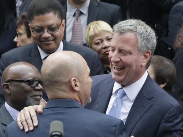 Democrat Bill de Blasio embraces a supporter on the steps of City Hall on Monday.
