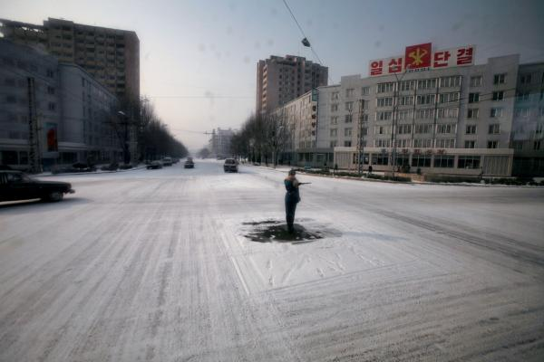 A traffic guard goes through the motions in the capital of Pyongyang, though streets are almost empty of cars.
