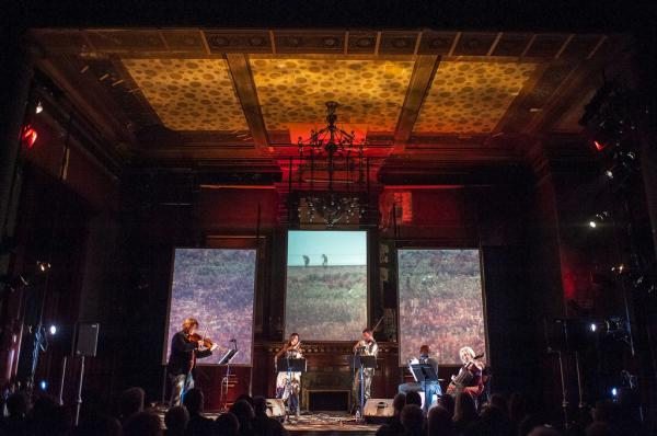 Ethel performs its <em>Documerica</em> program, featuring photos from Environmental Protection Agency archives, and music by composers including Vietnam veteran Kimo Williams, at the Park Avenue Armory in 2012.
