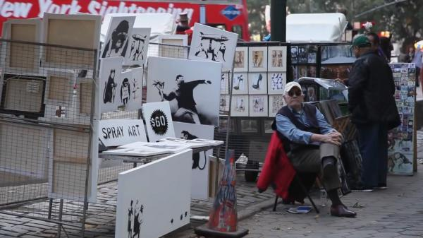 An image from a video posted by Banksy shows a man representing the artist staffing a sidewalk stall featuring signed works for $60. Banksy says he only made $420 Saturday, with one customer negotiating a 2-for-1 discount.