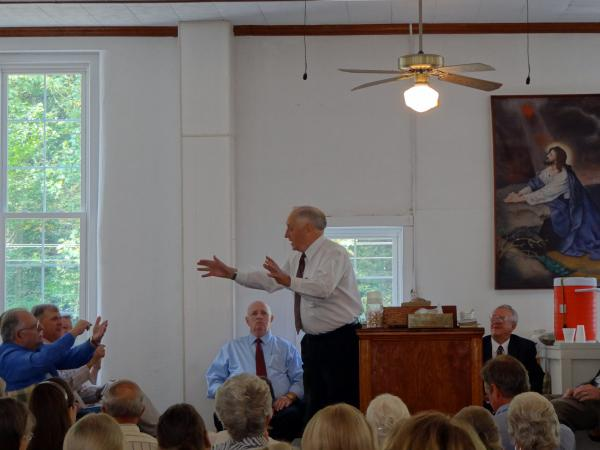 Church elder Elwood Cornett preaches at a recent reunion of Old Regular Baptists. Brother Don Pratt is seated behind him in a blue shirt and tie.