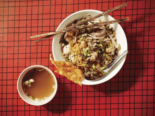 Ricker says this noodle dish translates roughly from the Thai as spicy, sweet, tart noodles with pork, peanuts and herbs.