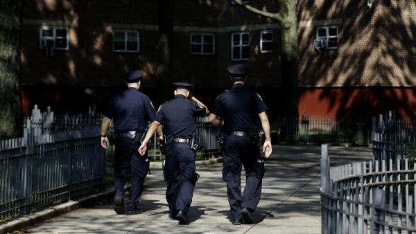 New York police officers walk through a Brooklyn housing development in August.