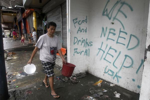 A resident walks past a wall with a graffiti calling for help in Tacloban. Rescue workers tried to reach towns and villages in the central Philippines on Tuesday that were cut off by the powerful typhoon.