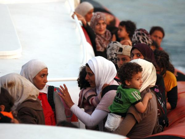 A boatload of refugees, including Syrians, is picked up by an Italian coast guard rescue boat off the coast of Sicily on Sept. 20.