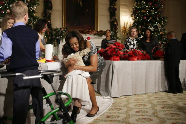 First lady Michelle Obama hugs a girl at the State Dining Room of the White House.