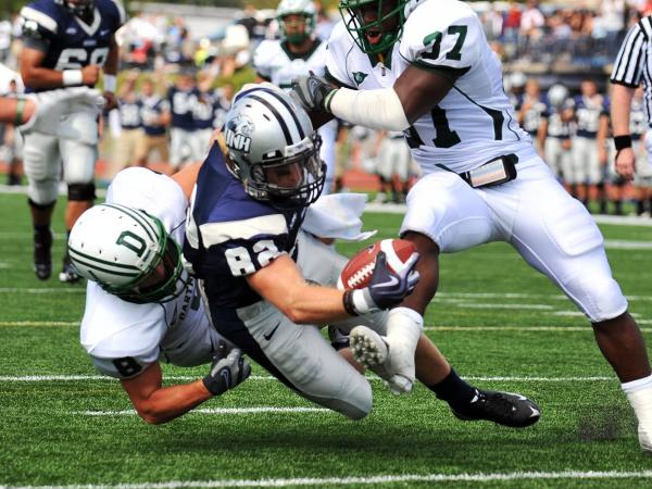 Dartmouth defenders sandwich a New Hampshire wide receiver during a game in Durham, N.H., in 2009.