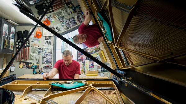 Some Steinway company representatives and employees — like Wally Boot, pictured here — have been working for the company for decades. Boot is the last person to touch every piano that leaves the factory in Queens, N.Y.
