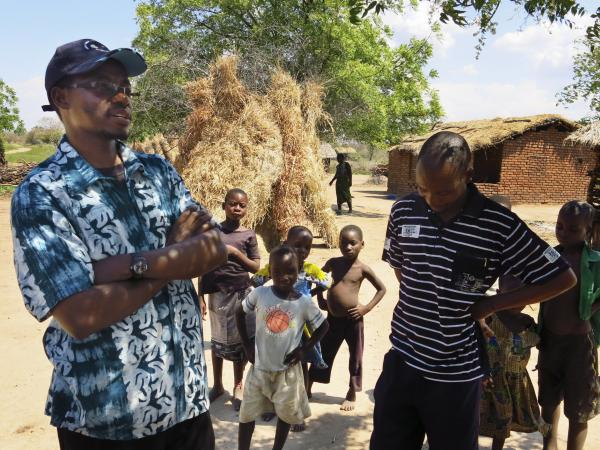 Victor Mughogho (left) is the executive director of Eagles Relief and Development, a nonprofit organization that's helping farmers adapt to climate change. He talks with villagers in Jasi, where his group has also donated goats so that people can sell the offspring if their harvest falls short.