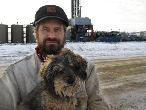 Donny Nelson with his dog Lucky. There are more than a dozen drilling rigs near his family's property.