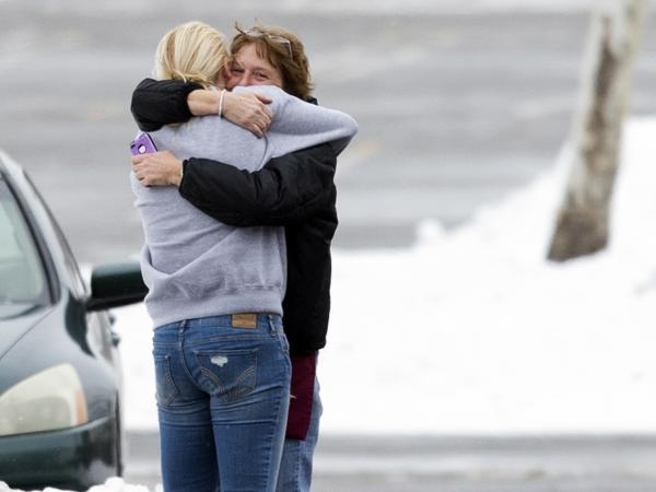 Two people embrace in the parking lot at the scene of a shooting Saturday at the Mall in Columbia in Columbia, Md.